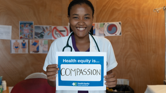 """Dr. Catherine Scipion wears a white doctor's coat with a stethoscope draped around the back of her neck. She holds a white sign with a blue border that says """"Health Equity is...Compassion"""""""