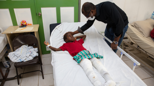 A yong boy in a red t-shirt lays in a hospital bed. He has two broken legs, which are wrapped in white bandages. A doctor wearing a black shirt and a white medical face mask leans over and touches the boy's head.