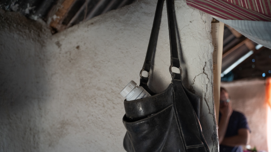 Marie's medication hangs from a bag on the wall of her home.
