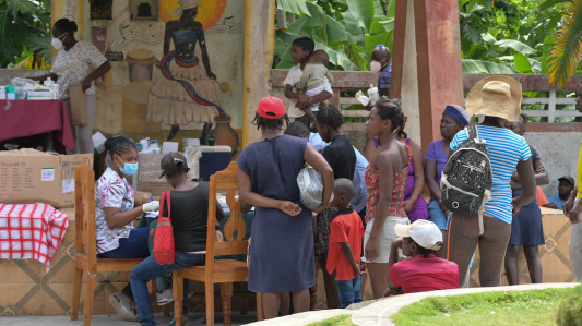 A crowd of patients wait to be seen by a community health nurse at an earthquake mobile clinic.