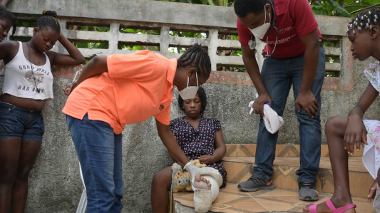 Two doctors examine a woman's broken leg. The woman sits on a low wall, her leg is in a cast and is stretched out before her. One doctor leans over and touches her cast. The other doctor looks on.