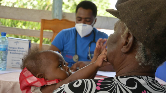 A woman holds a baby while recieving care at an earthquake mobile clinic. The baby reaches out and touches the woman's face while a doctor looks on in the background.