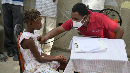 A doctor listens to a young girl's heart using a stethoscope at an earthquake mobile clinic.