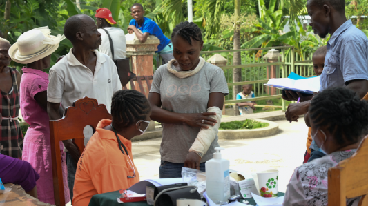 A woman with an arm cast speaks with a community health worker at an earthquake mobile clinic. A crowd of other patients stand behind her.