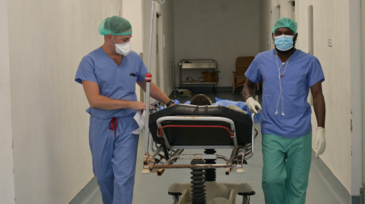 Two surgeons take a patient into an operating room. The surgeons lead a hospital bed down the hall. They both wear blue scrubs, a medical mask, and green hair nets.