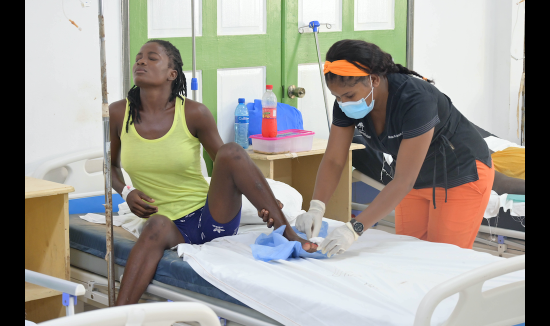 A woman sits on a hospital bed while a clinician tends to her foot. The woman is wearing a bright yellow tank top. She looks to her left and appears to be in pain. The clinician stands to her right and tends to the woman's wounded foot. The clinician wears an orange headband, blue medical mask, and black and orange scrubs.