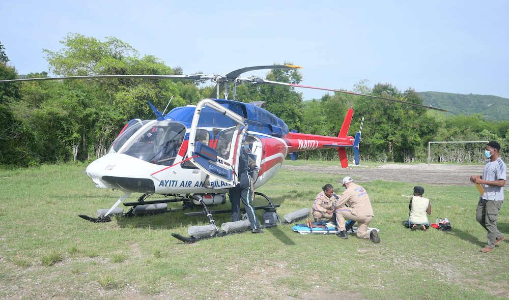 A helicopter helps to transport an earthquake survivor to St. Boniface Hospital. The red, white, and blue helicopter sits in a green field. Two aid workers wearing tan jumpsuits kneel next to the helicopter and tend to a patient.