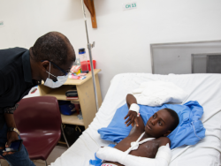 Dr. Pierre leans over to talk to Albertiny, a 9-year-old earthquake patient who received orthopedic surgery for a broken elbow. Dr. Pierre wears a black shirt and a surgical mask. He stands to the left of Albertiny's hospital bed. Albertiny lies in bed; his left arm is in a white cast up to the shoulder.