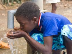 boy drinking water from well pump