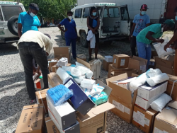 A group of people unpack cardboard boxes full of medical supplies. Some of the boxes are open and you can see blue medical masks and packages wrapped in a white wrapper. A man in black jeans and a yellow polo shirt bends down to unpack the boxes. Nurses in blue t-shirts in the background observe. There is a white ambulance with green lettering in the background. The ground is white and grey gravel.
