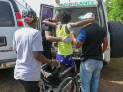 A woman is helped into a wheelchair. A white ambulance is in the background with its back doors open. A woman in a bright yellow tank top has her arms around two people on her left and right. They are helping her sit into a wheelchair. The woman on the right wears a white shirt and a colorful headscarf. The man on the left wears a black t-shirt and a white cap.