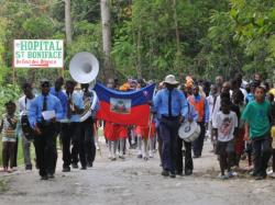 Parade of people carrying the Haitian flag in front of the St. Boniface Hospital sign