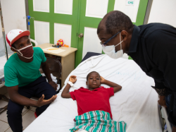 A young boy wearing a red t-shirt lays in a hospital bed. His father sits in a chair to the left of the hospital bed. A doctor stands to the right of the hospital bed. The doctor and the patient's father talk.