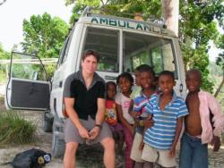 Matt in Haiti smiling with a group of children