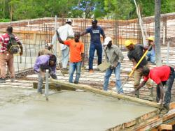 Workers laying the cement for the maternal health center
