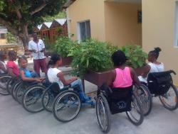Group of people in wheelchairs tending to a raised garden
