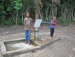 Two young children pumping water