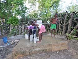 Group of children pumping water into containers